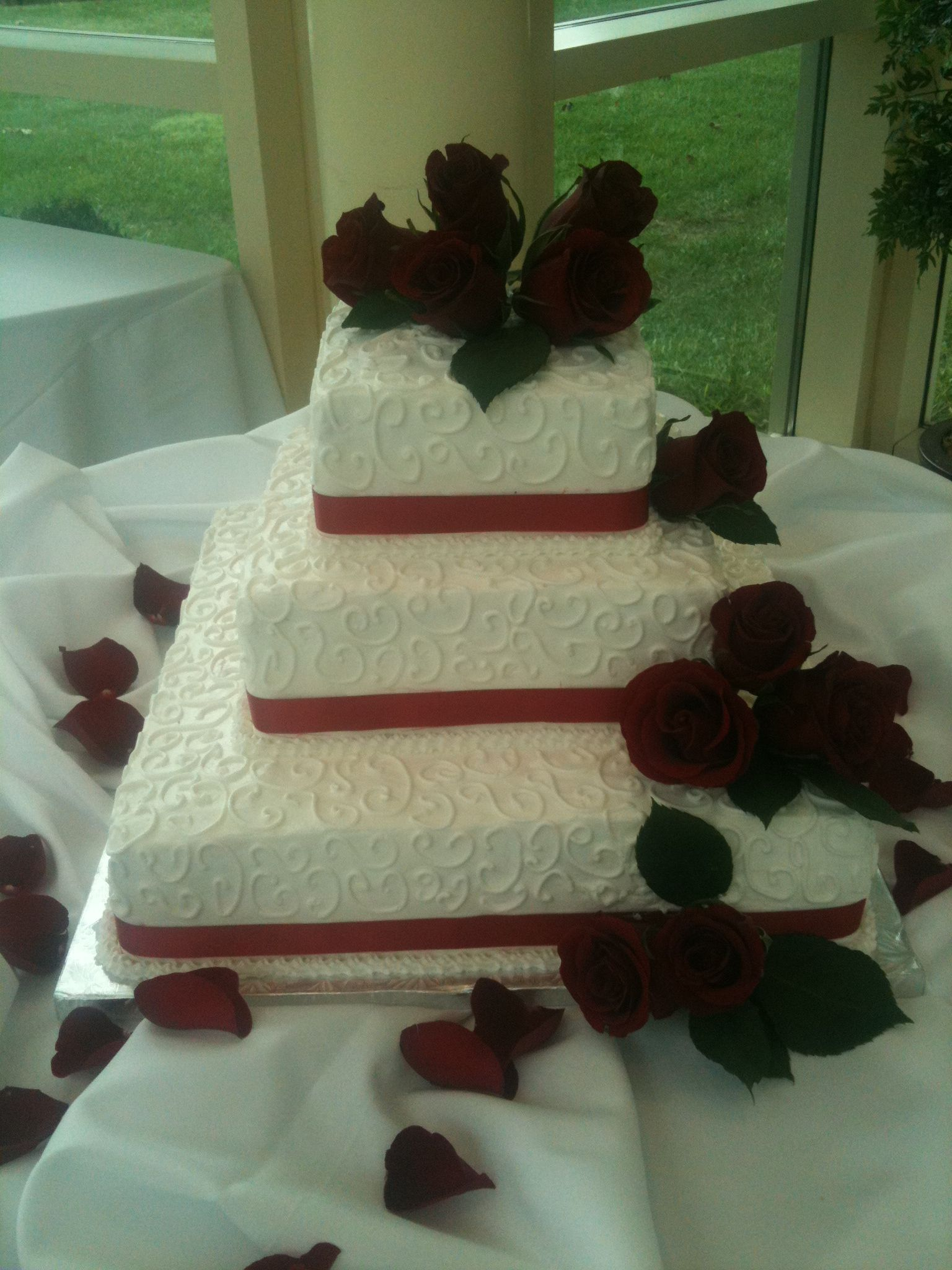 square tiers wedding cake with red ribbon and red roses at newton
