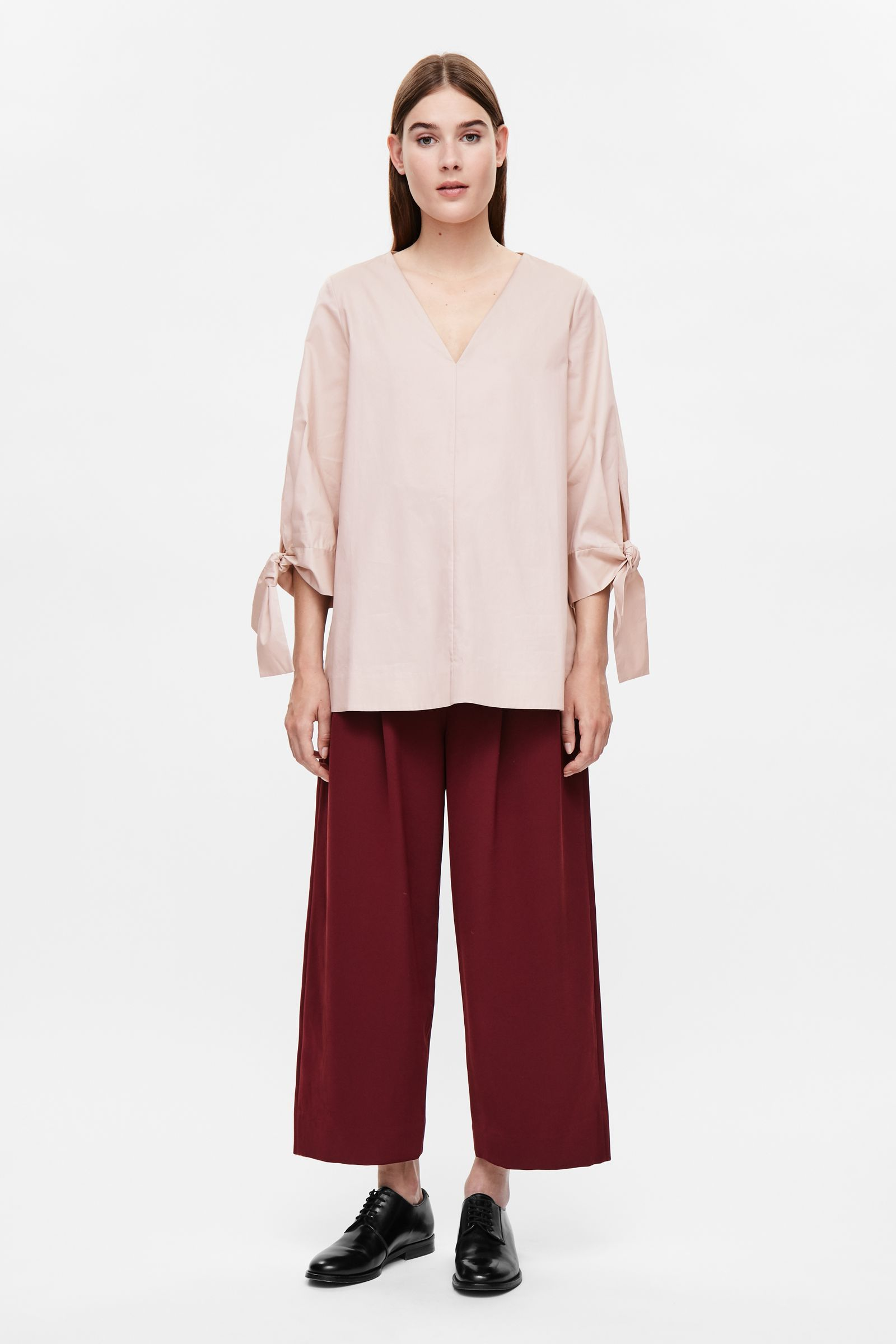 This loose-fit top is made from soft cotton poplin with oversized tie cuffs and split sides. An A-line fit, it has a deep v-neckline, 3/4 sleeves and clean edges.