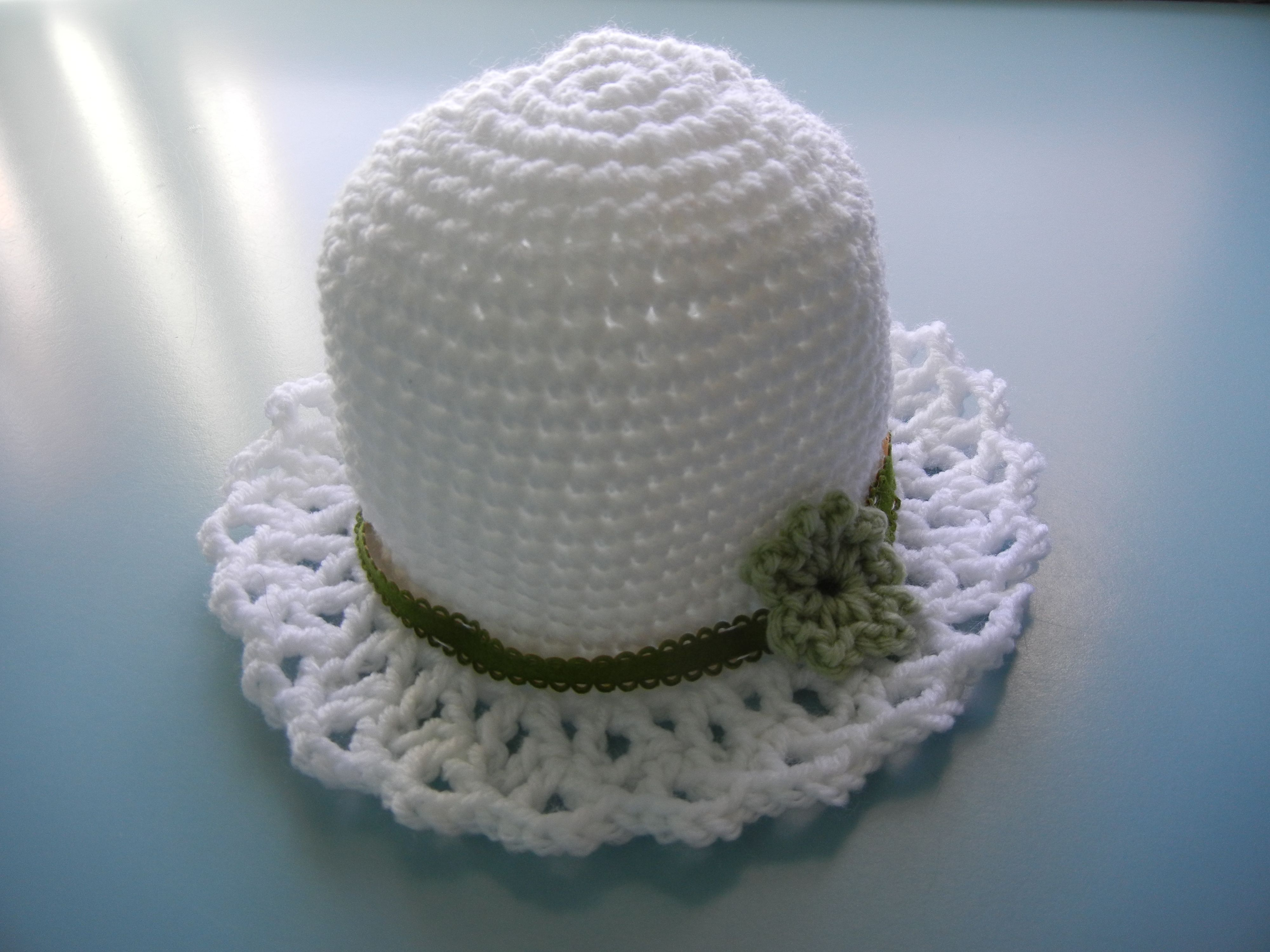 White hat with an olive green band and flower for a child.