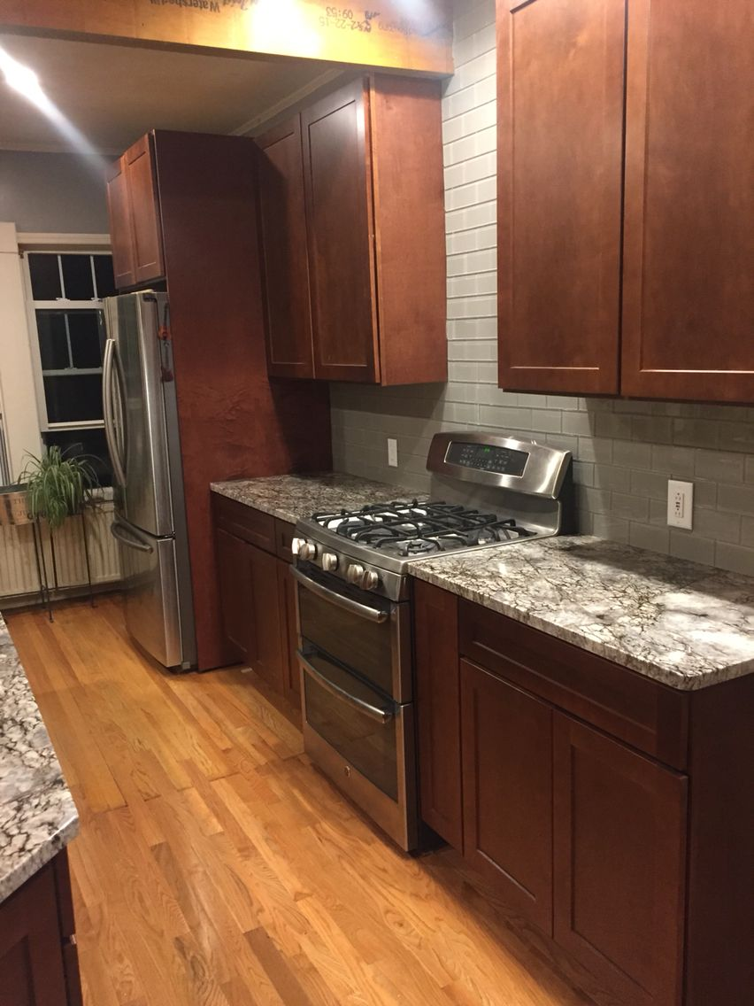 Maple Mocha Cabinets Blue Flower Granite Warm Grey Tile Backsplash Stainless Steel Appliances Kitchen