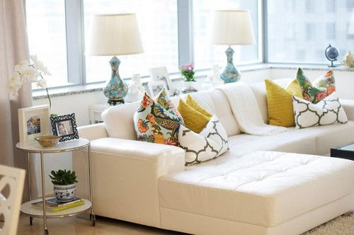 beautiful patterned pillows on a clean lined (but still tufted!) off-white sectional in an urban apartment.