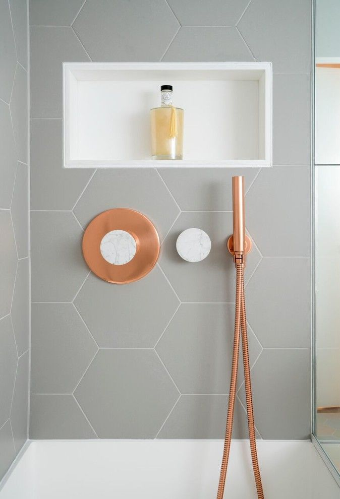 This bathroom features copper and marble fixtures next to light gray this bathroom features copper and marble fixtures next to light gray hexagon tiles mozeypictures Choice Image