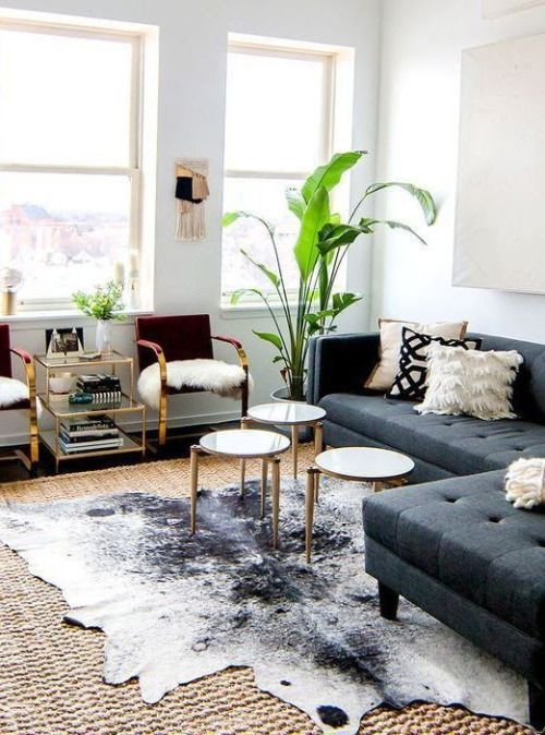 A Living Room Space With A Faux Cowhide Rug Art Nouveau Fireplace And Touches Of Gold Lazyboy Rugs In Living Room Hide Rug Living Room Cow Rug Living Room