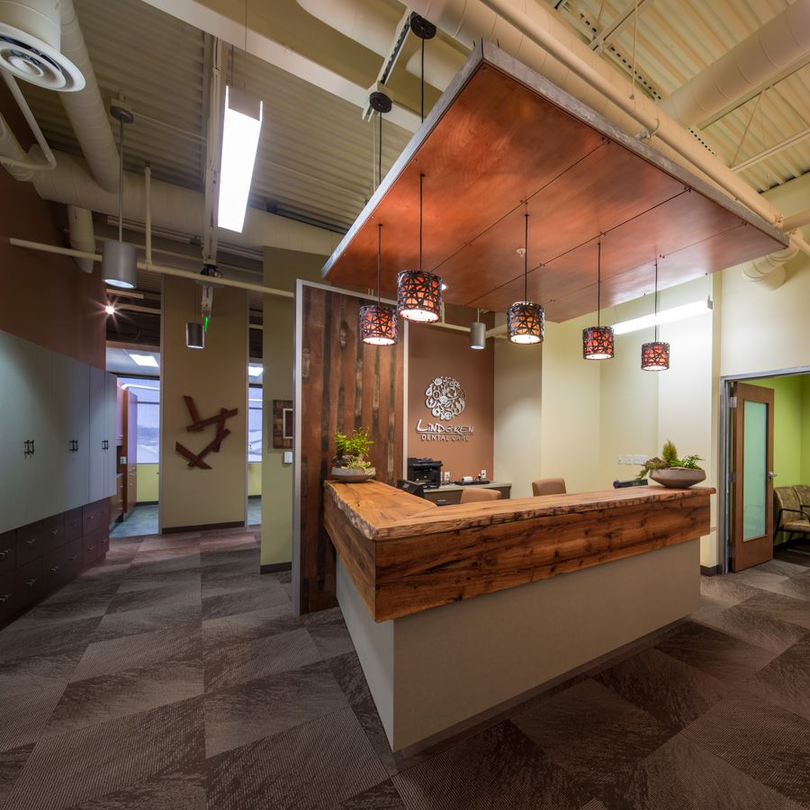 Sustainable dental office utilizing reclaimed wood as a reception desk and artwork.