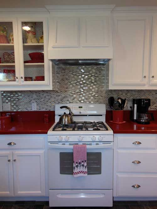 Kitchen With White Cabinets Smoked Gl And Silver Hardware Set Off By Caesarstone Red Countetops A Shimmery Black Splash