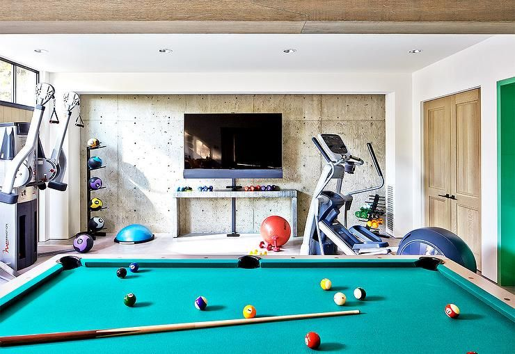 Basement game room and gym boasts a pool table facing a flatscreen