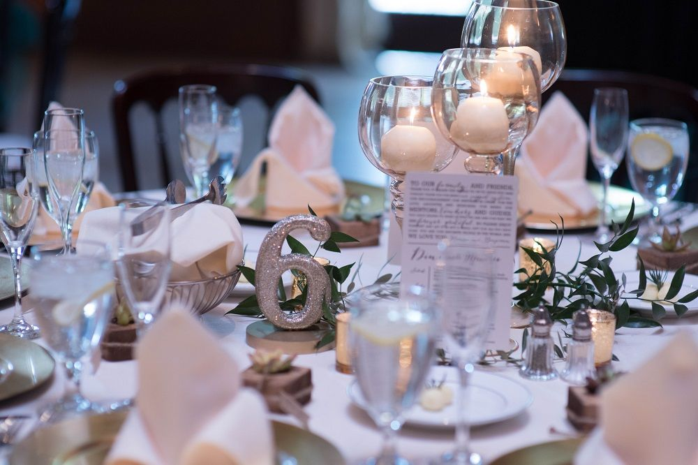 White linen tables with greenery and cacti