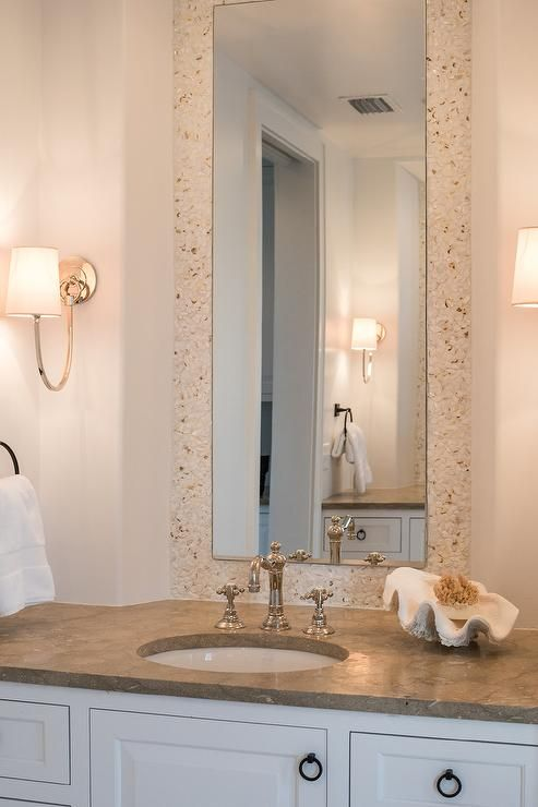 white and cream bathroom features a tall mirror bordered