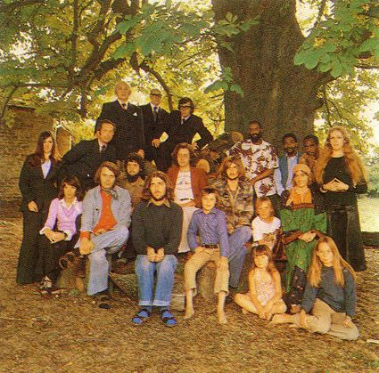 Mike Oldfield and musicians from the recording of Ommadawn. Top Left: hereford Brass Band; Top Right: African Drum Ensemble Jabula; Middle Row: Mike Oldfield at center right behind boy, sister Sally Oldfield also in middle row; Front Row: Mike's brother Terry Oldfield at center
