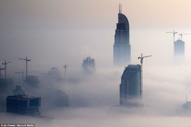 Dramatic images of Dubai's skyscrapers poking through a carpet of fog at night