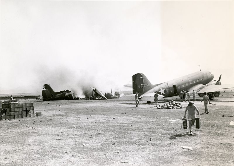This picture comes from Port Moresby, New Guinea. Though credited as having been used in September 1943 for the Dayton Daily News, the caption notes that the picture was originally taken in 1942. It was taken following a Japanese air raid on the airfield, which destroyed one C-47 transport at left, and has apparently set fire to the other C-47 on the right. If one looks closely, they can see where heat has wrinkled the skin of the aircraft, just behind the cargo door. The man running towards…