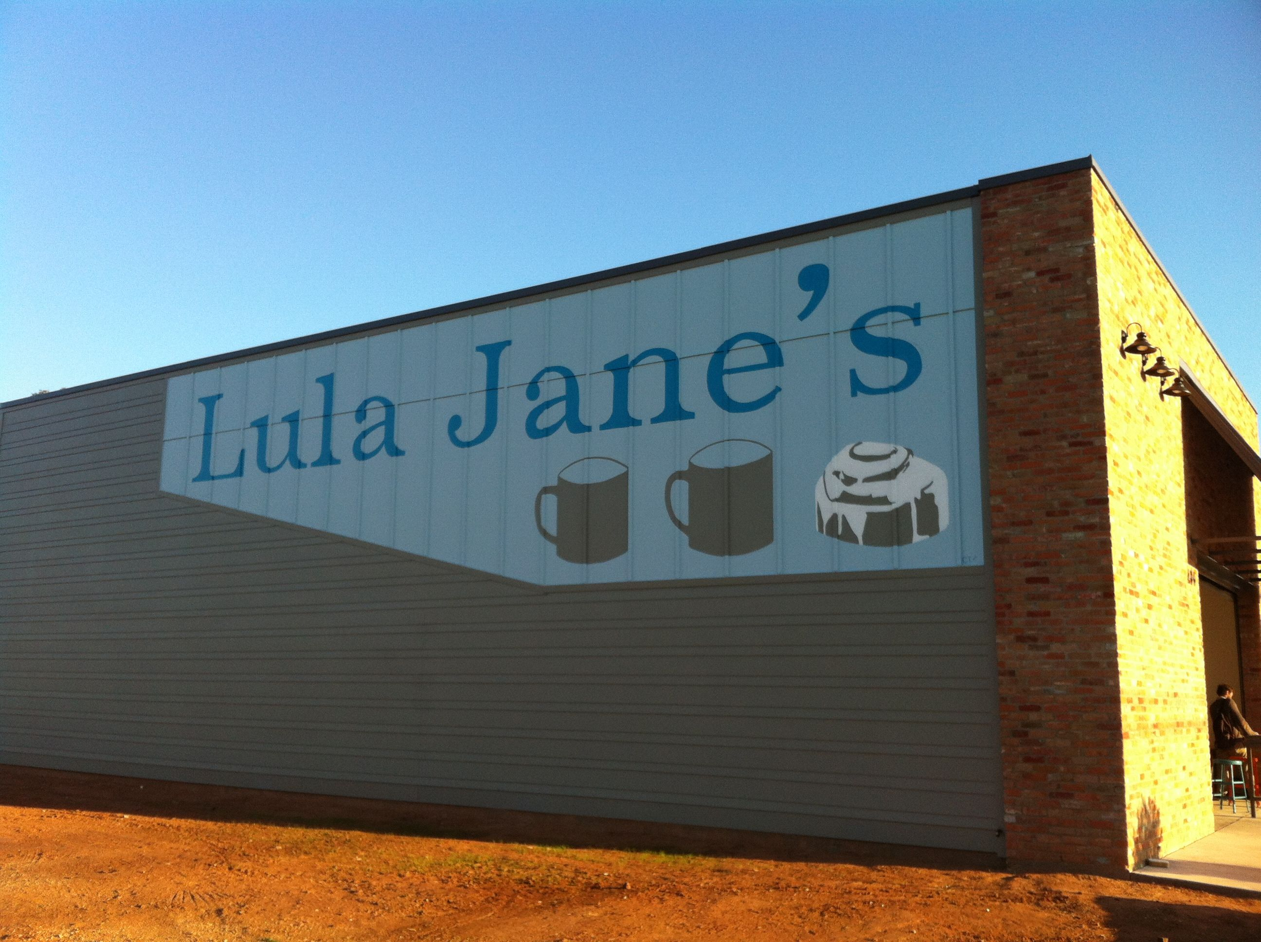 Image of the restaurant Lula Jane's in Waco, TX. The name of the restaurant is painted in blue on the side of a building, and there are two mugs and a cinnamon roll underneath.