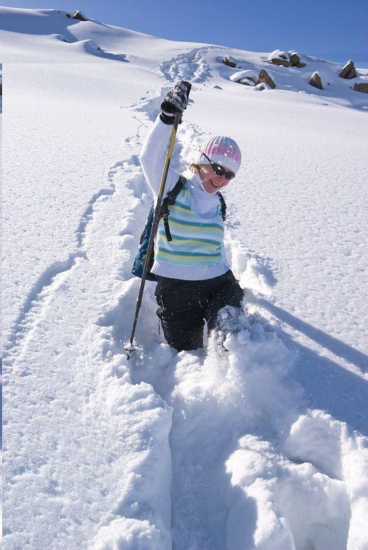Férias activas.  Mulher do russo em um caminho de neve de sorriso em montanhas do inverno.  Tours Activos.