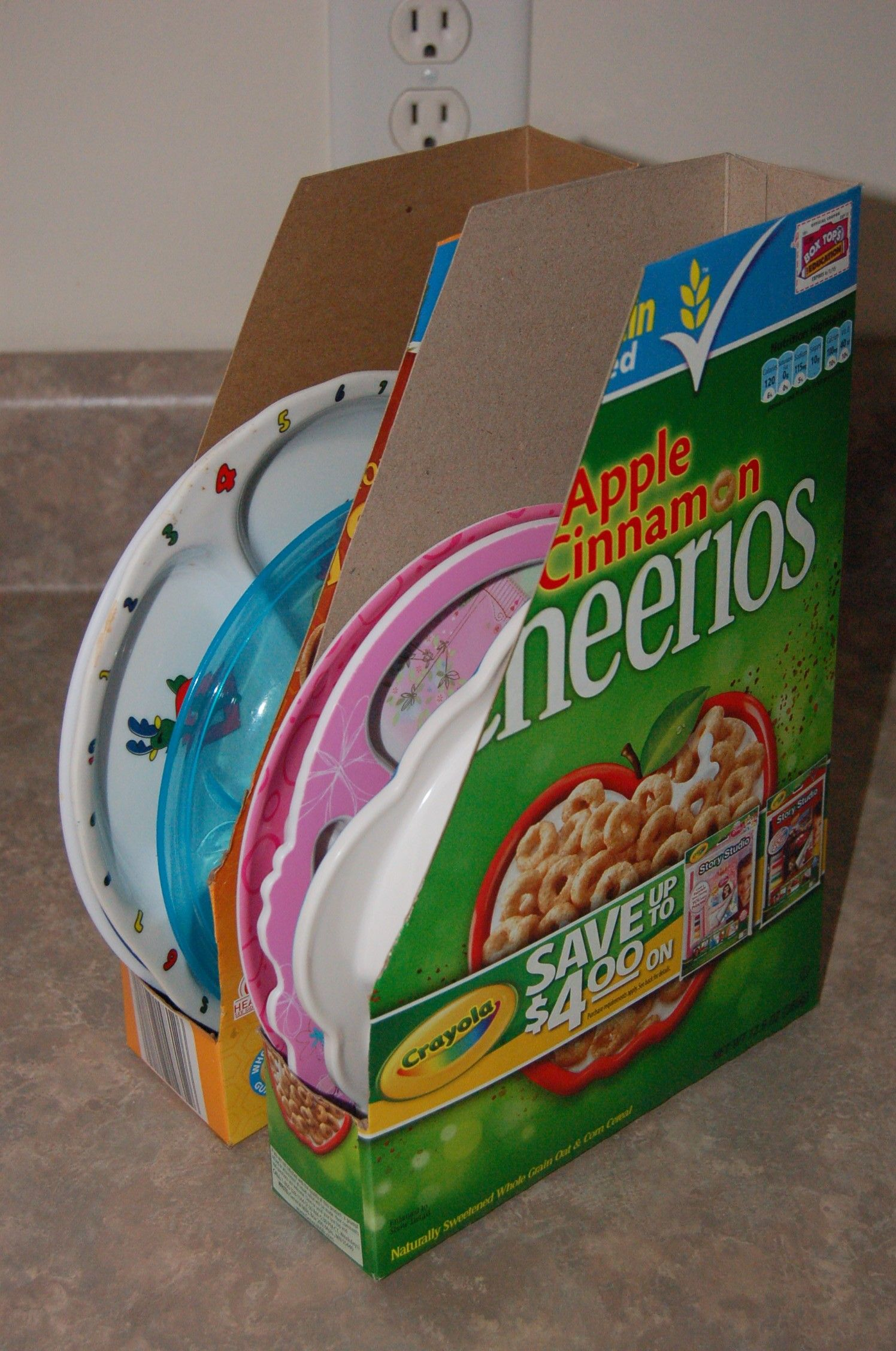 My daughter's plates were so annoying to stack in the cabinets since they're all different sizes and have all different styles. So, I made these handy plate organizers from cereal boxes. No more plates falling in my face when I open the cabinet door and I now have more space in there as well!