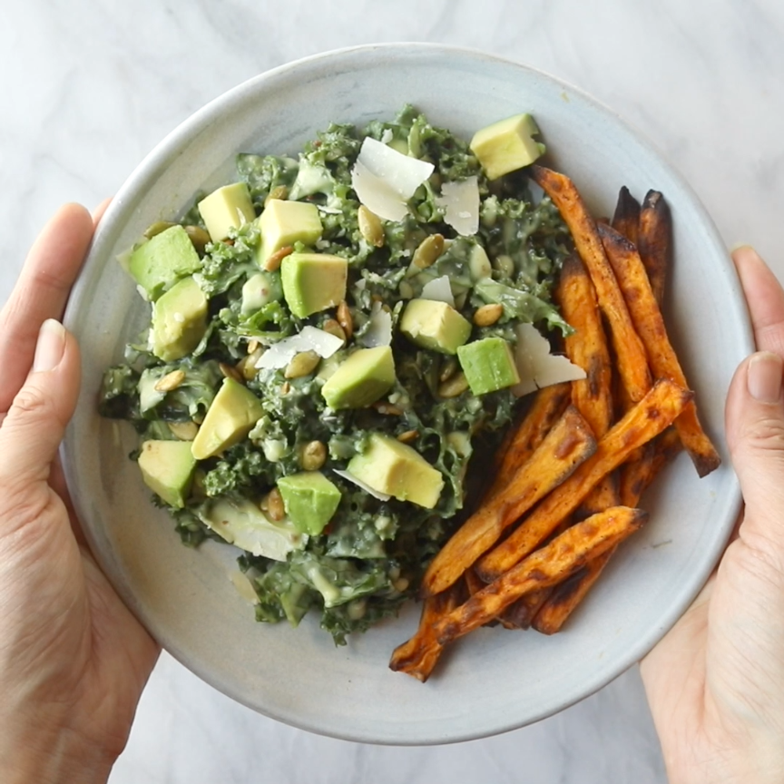 Okay, Avocado Kale Caesar Salad is a life-changer! Kale, avocado, and crunchy seeds drenched in a quick creamy avocado caesar dressing that can easily be made vegan, too. Toss some crispy sweet potato fries in are you are SET FOR LIFE. #salad #vegan #vegetarian #meatlessmonday #recipe #healthy | pinchofyum.com #quickdinnerideas
