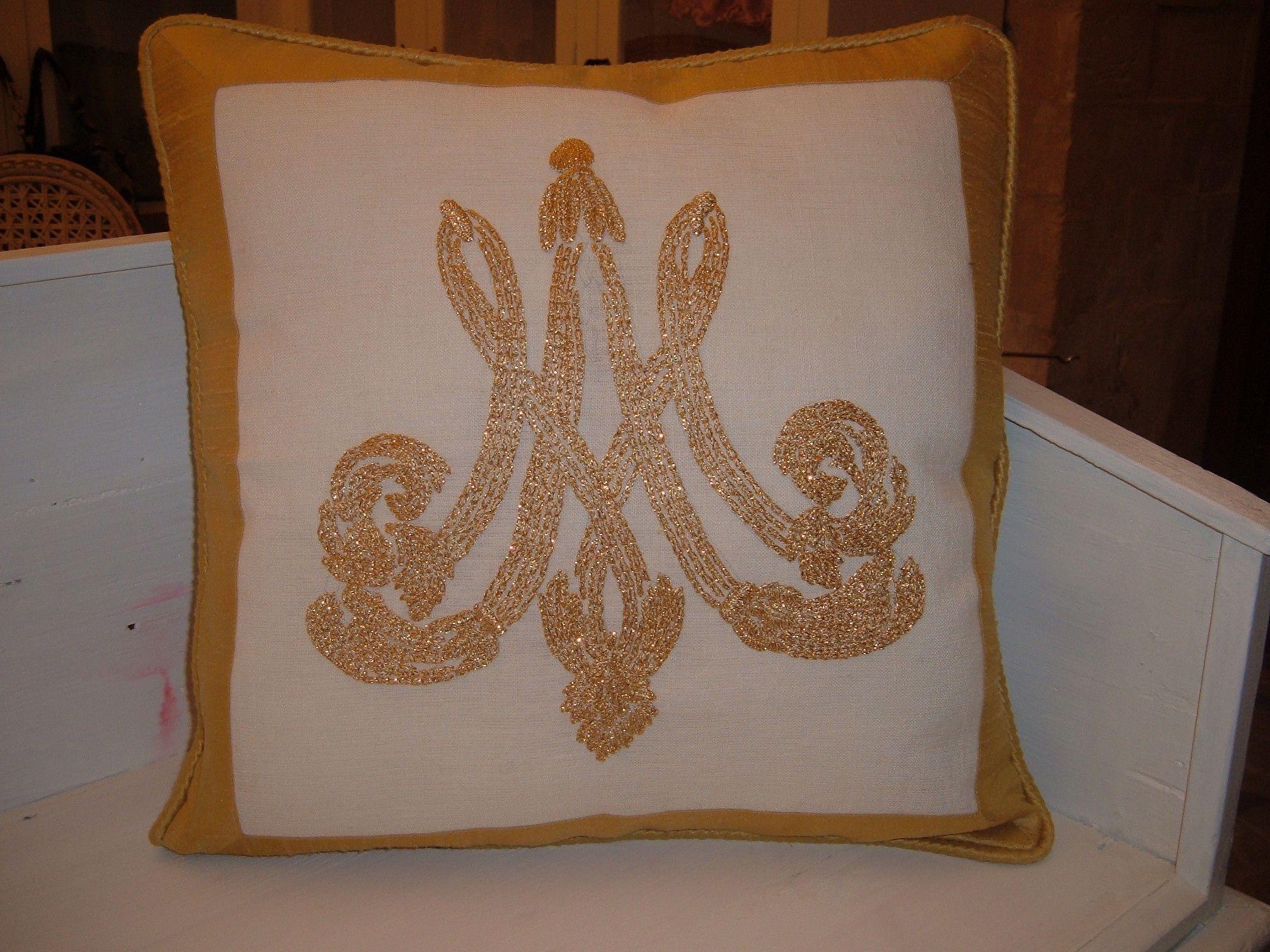 Cuscino barocco con monogramma monocromatico oro.