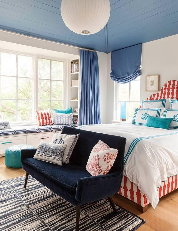 Red and blue girl's room features a blue plank ceiling accented with a white paper lantern over a red print bed dressed in white and turquoise blue monogram bedding alongside a blue velvet settee placed at the foot of the bed atop a navy rug.