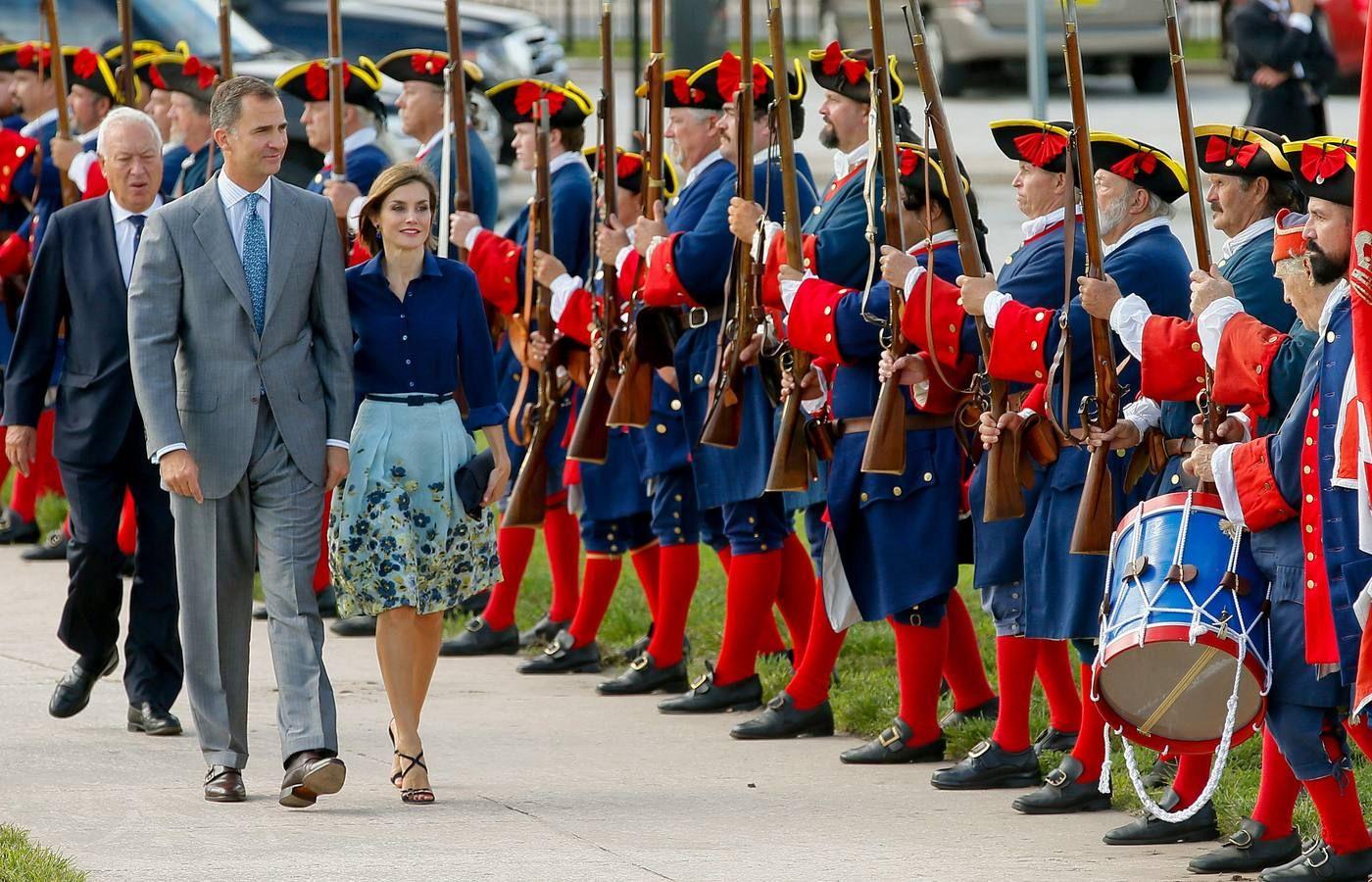 El rey Felipe VI y la reina Letizia seguidos del ministro de Asuntos Exteriores, José Manuel García-Margallo, pasan ante voluntarios ataviados con uniformes de época de la antigua guarnición española, durante la visita que han realizado hoy al Castillo de San Marcos en la ciudad de San Agustín