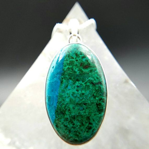 Check out this beautiful oval Chrysocolla crystal pendant set in 925 sterling silver. This pretty pendant has malachite inclusions that is typical with the formation of chrysocolla crystals.   Chrysocolla is a hydrous copper silicate crystal that contains a high copper content which is helpful in healing any issues around the throat and heart chakra areas. This crystal has a soothing and cooling energy that helps to alleviate stress and anxiety. Wear this pendant to help you speak from the…