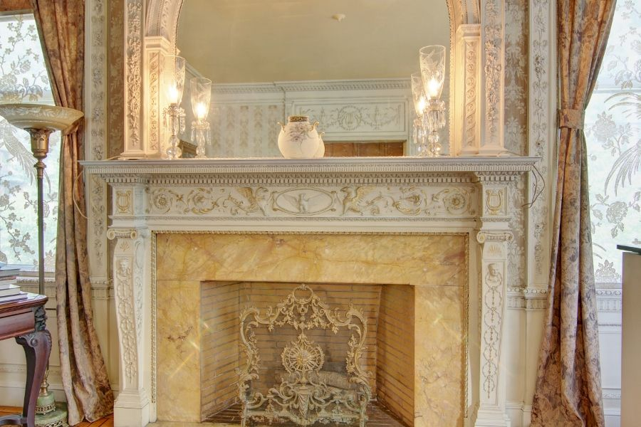 A golden marble wood-burning fireplace with a classic dentil mantel surround.