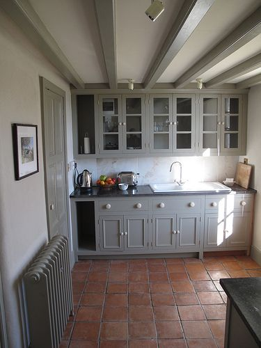 Grey cupboards and terracotta tiles.... try Farrow and Ball Manor House Grey