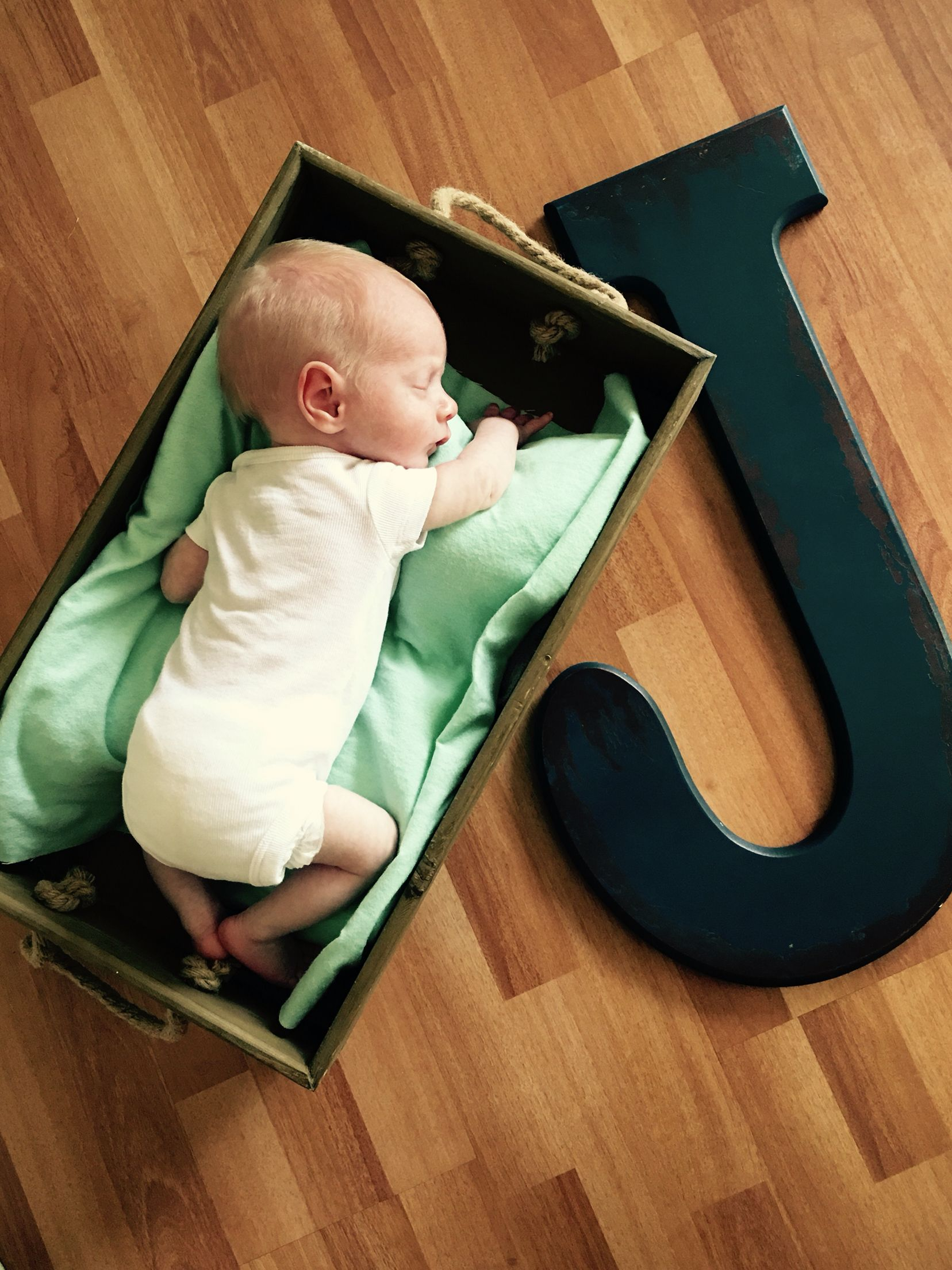 Newborn photo, wooden crate, wooden letter. Jax Walker