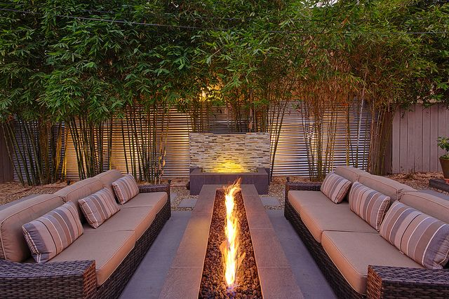 Gorgeous outdoor firepit, furniture and water feature, offered lots of privacy by a living wall of bamboo!