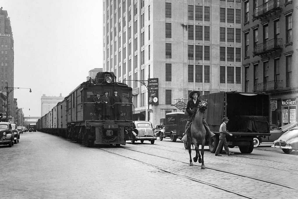"""During the 1840s, the city of New York mistakenly allowed the building of train tracks along Manhattan's West Side. Soon after, trains and street-level vehicles collided in frequent accidents, leading the Eleventh Avenue freight line to be nicknamed """"Death Avenue."""" To provide more safety, the West Side Cowboys were formed, a contingent of several men on horseback who rode ahead of the trains to signal their arrival. In the 1930s a large project to reconfigure the West Side included the…"""
