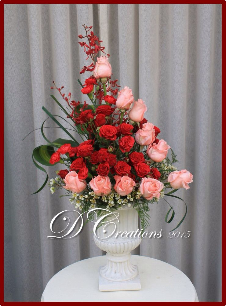 Inverted number 4 with red and pink roses in an urn