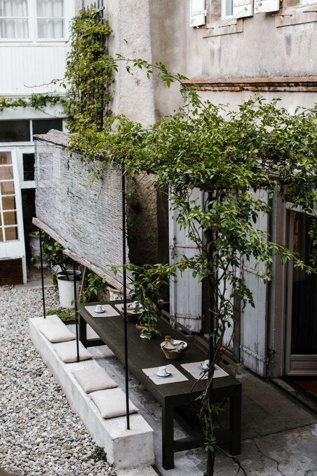 Photo of Søt uteservering for en restaurant med grøntområder. Enkel utendørs courtya …