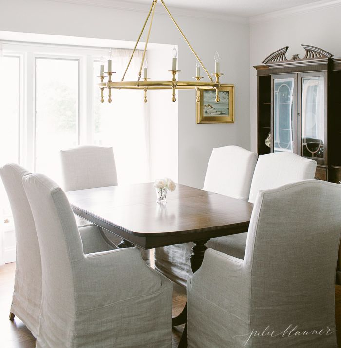 Traditional Dining Room With Slipcovered Chairs And Brass Chandelier