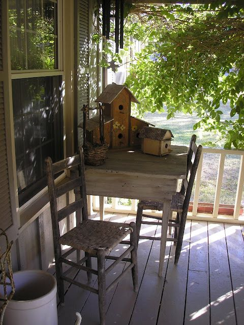 Rustic Porch...with prim birdhouses on an old table.