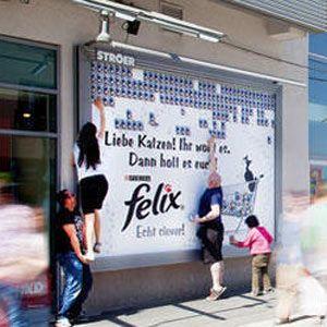 """La marca de comida para gatos Felix ha dejado durante diez días en las ciudades alemanas de Dresde, Núremberg y Stuttgart unas golosinas """"pegadas"""" en los carteles publicitarios. Los dueños de los felinos debían, desde luego, emplearse a fondo para conseguir las muestras alimenticias que estaban colgadas en lo alto de los carteles. Unos brazos largos o que a uno le hagan el estribo ayudan."""