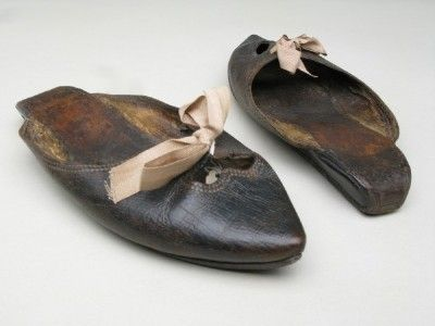 Manchester City Galleries item 1947.1057,    1780-1800 shoes & pattens  Pointed leather toes. Fronts with shaped opening, and 2 holes for ties. Sole only, with wedge under instep.