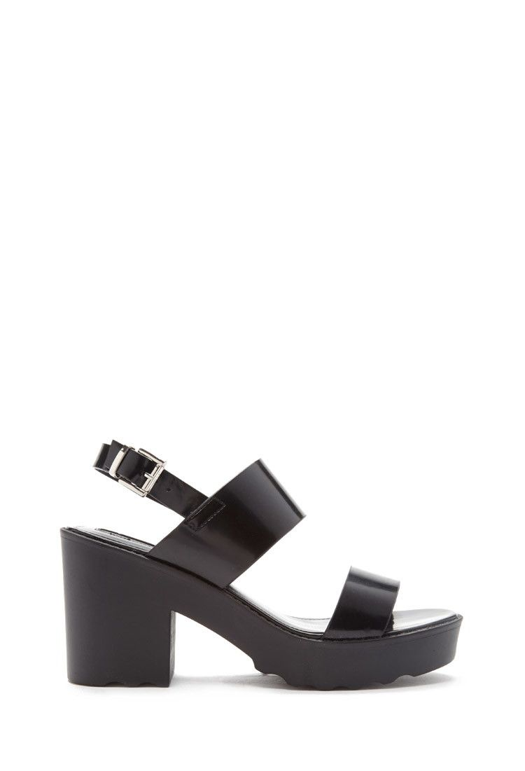bda152bb555 A pair of patent faux leather sandals with a buckled ankle strap and a platform  lug sole.