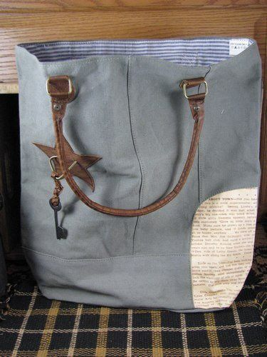 Newsprint Patch Tote Bag This canvas tote bag features an army green canvas material with leather handles, a newsprint patch on the bottom corner and a leather star with a key hanging from it. It meas