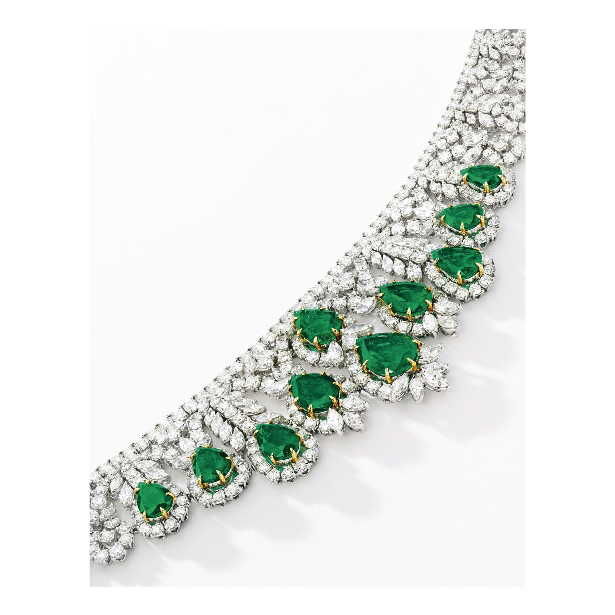 The necklace set with ten pear-shaped emeralds, to diamond-set links of graduated floral motif, suspending from a line of brilliant-cut diamonds; and pair of pendent earrings en suite; the emeralds and diamonds altogether weighing approximately 47.92 and 55.00 carats