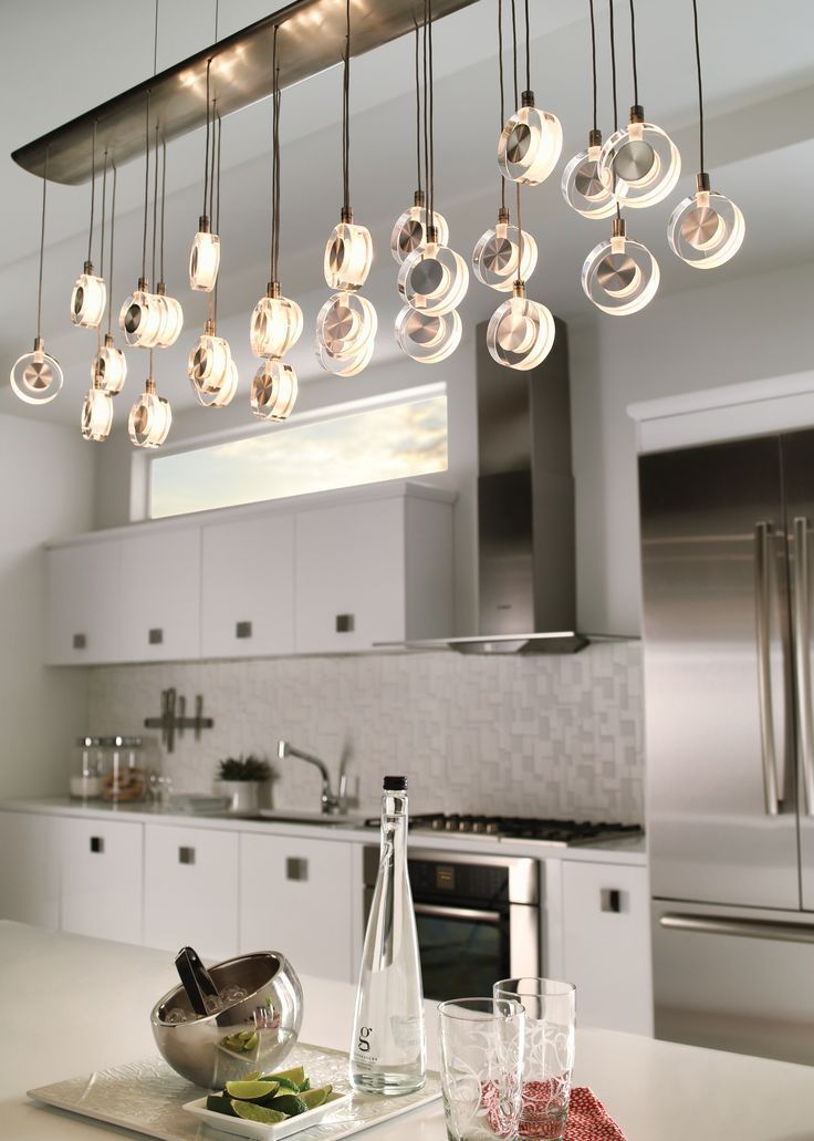 Bling chandelier by lbl lighting is a gently curving linear fixture that suspends 26 discs of transparent crystal with sandblasted interior and decorative