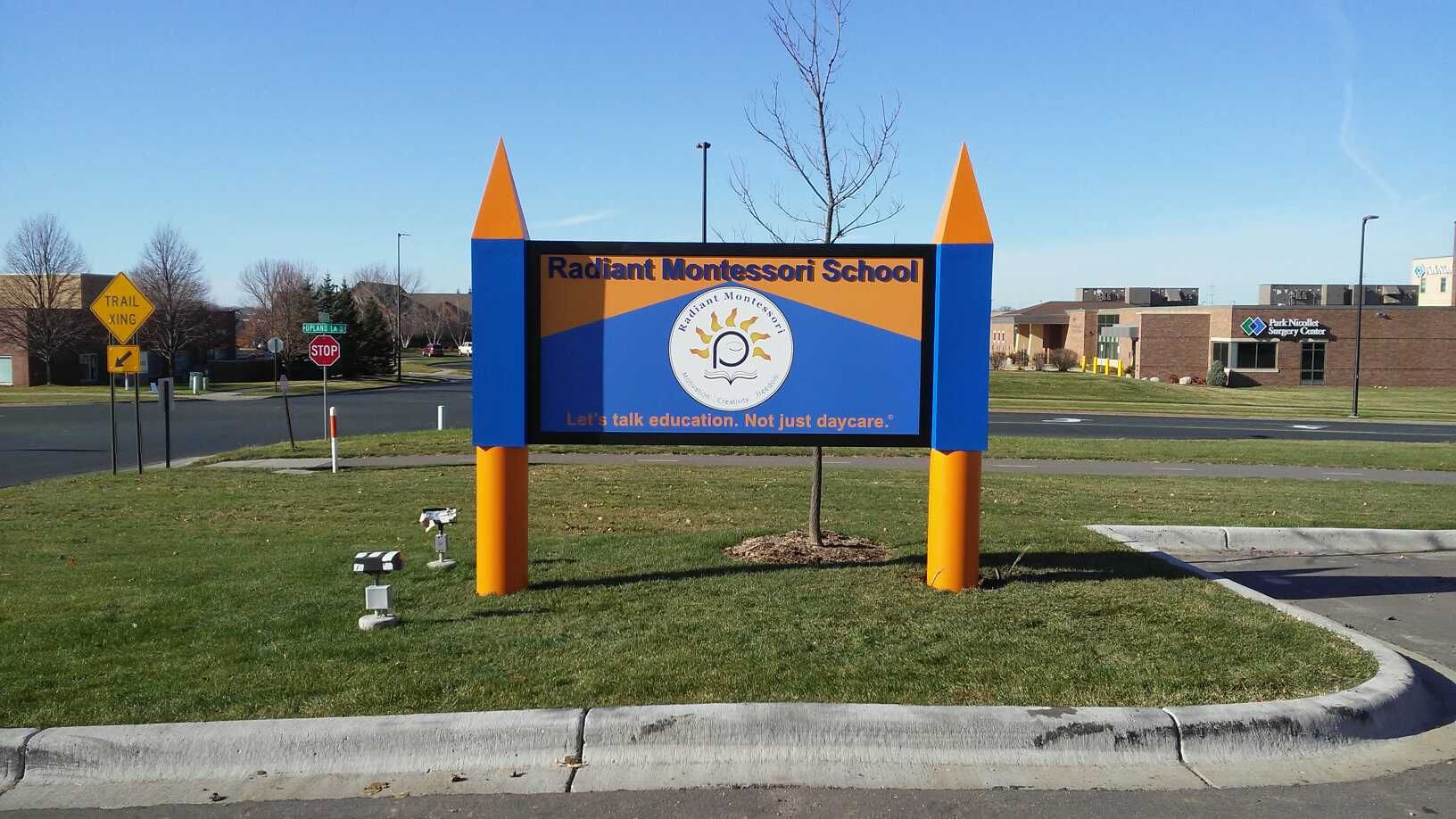 Daycare sign for a local Montessori School adds a creative twist to the sign poles!
