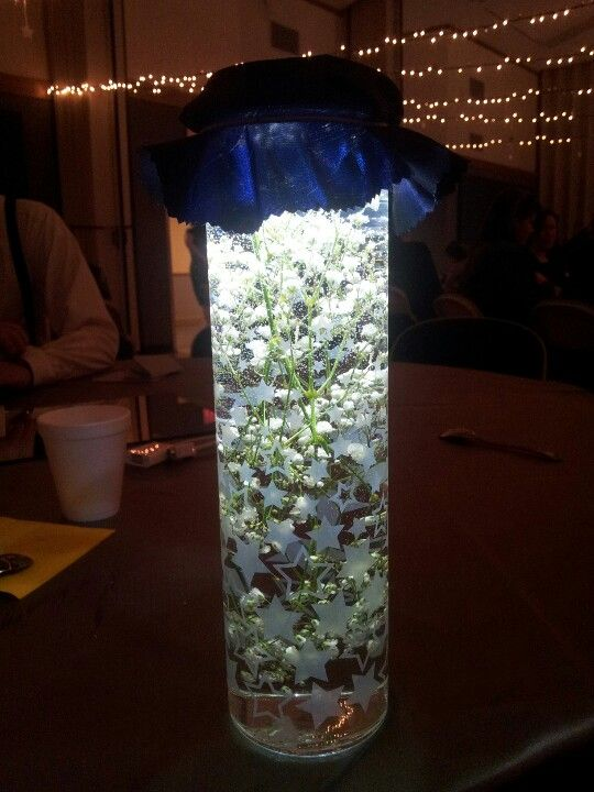 Wedding reception center piece. Battery powered LEDs in the top covered by cloth.  Baby's breath in water in the vase.