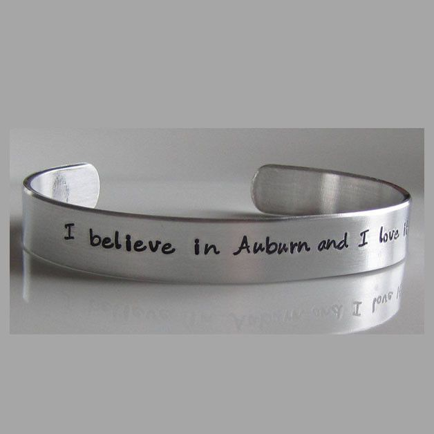 """This is one of my hand stamped, cuff bracelets inspired by The Auburn Creed of Auburn University in Auburn, Alabama. I created it on jewelry grade aluminum. Aluminum is great because it will NOT tarnish and it takes the stamps so beautifully. I can create a nice, deep impression which stands out nicely. I cut, file, polish, stamp and color these bracelets 100% by hand with care. It reads """"I believe in Auburn and I love it"""". The cuff can be adjusted for a custom fit."""