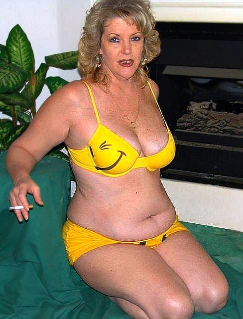 Mature Blond With Big Saggy Tits Kneeling Wearing A Yellow Bikini And Smoking A Cigarette