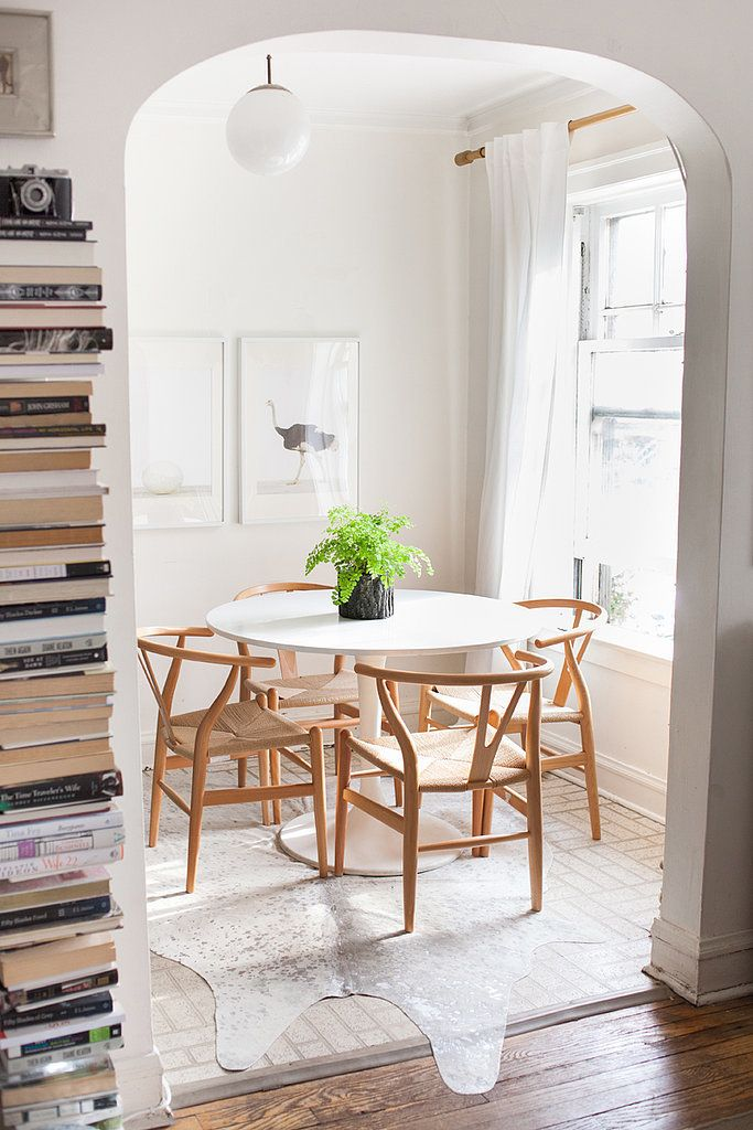 Modern, All White Dining Space With Cowhide Rug, Wood Chairs, And Stacked  Books