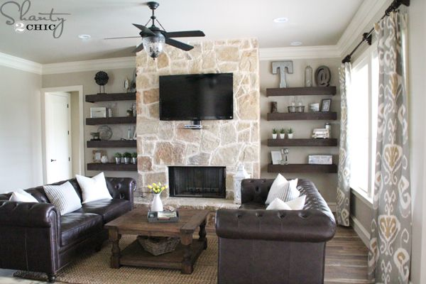 stone fireplace with mounted tv and bookshelves on each ...