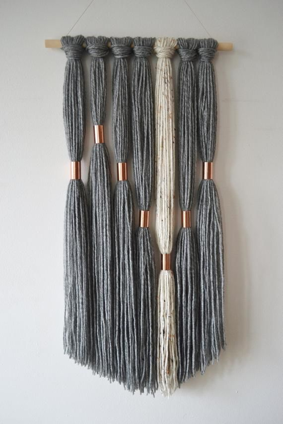ESME This modern and edgy wall hanging, comes in a grey and neutral color palette. Seven sections of hand-mixed yarn strands are divided by copper tubes. The entire piece is hung on a natural wood dowel and the fringe is cut in an asymmetrical shape. Modern inspired wall hanging is