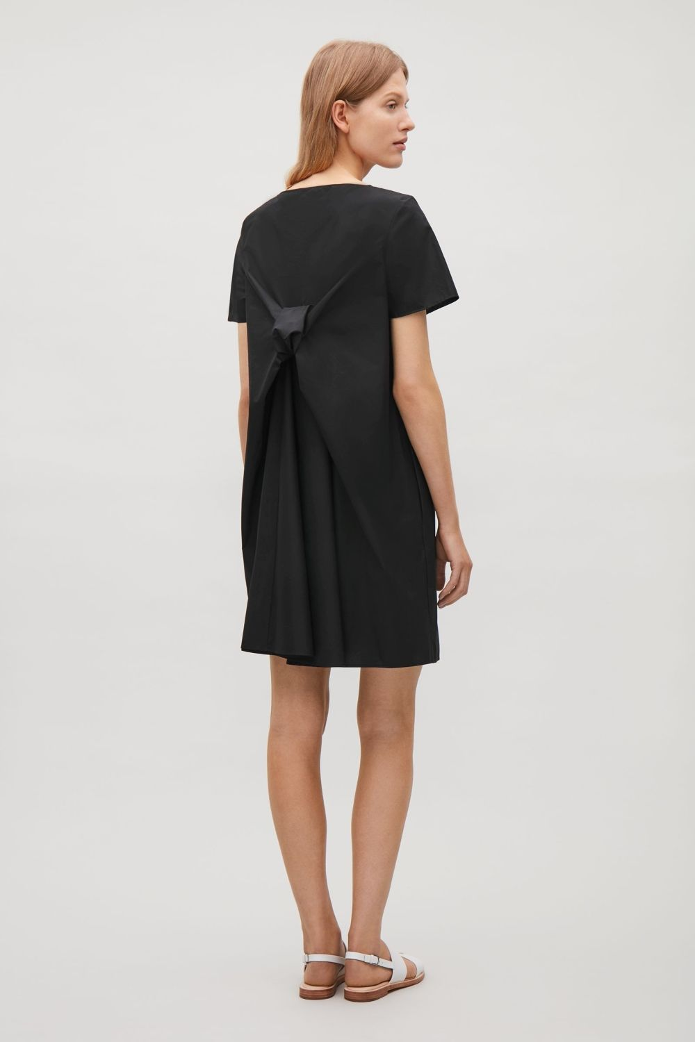A straight fit this shortsleeve dress has a voluminous draped bow