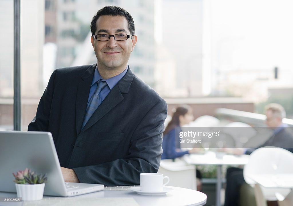 Smiling business man with computer in cafe. Mba degree