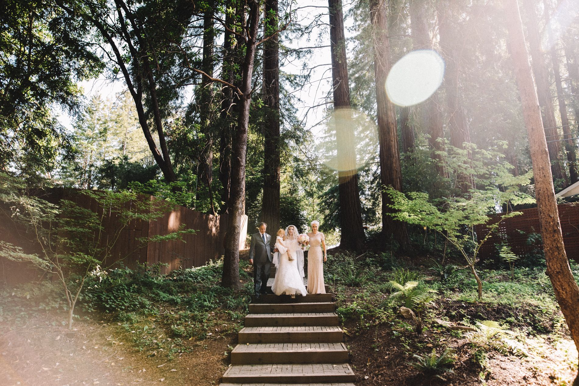 A Magical Moment Walking Down the Aisle   Amphitheatre of the Redwoods at Pema Osel Ling   Wedding and Event Venue   Santa Cruz Mountains, CA   Redwood Forest Wedding   Photo Courtesy of Ahava Studios