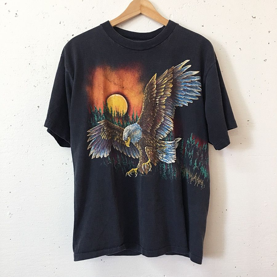 Vintage 1980's soaring eagle, black, graphic tee. Shirt is perfectly distressed and worn in. There's a few small holes in shirt. Graphic extends from the front around the side to back. Shirt is softly