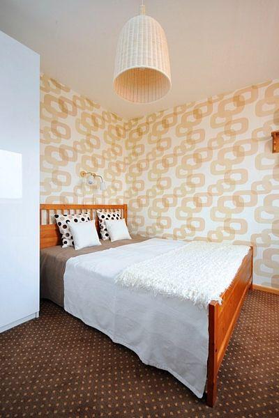 Rodičovské ložnici minimálních rozměrů dodala osobitý výraz tapeta, jejíž geometrický vzor efektně rozvíjí koberec i dvojice dekorativních polštářů.
